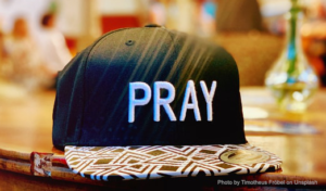 baseball cap with 'PRAY' on it